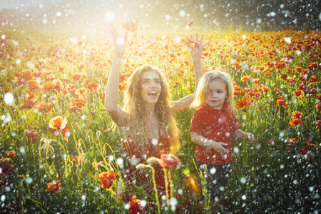 christmas new year snow concept love and family, happy mother and child in poppy field with flower sunny summer outdoor