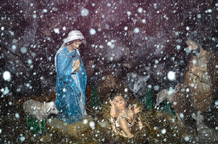 christmas new year snow concept Christmas Manger scene with figurines including Jesus, Mary, sheep and magi.