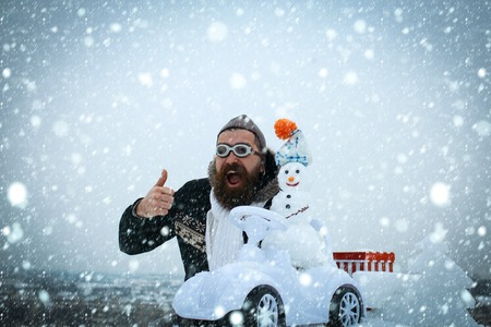 v Bearded man in pilot hat and glasses showing thumbs up. Excited hipster on winter landscape. Snowman driving toy car on white sky. Christmas and new year. Holidays celebration concept. Stock Photo