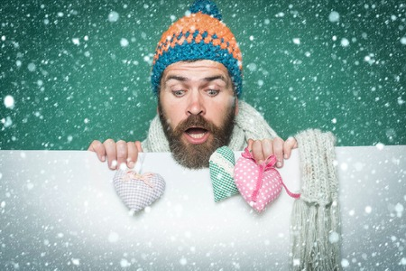 christmas new year snow Holiday celebration and party. Valentines day and love. Man with long beard hold heart pillow. Guy with surprised face in winter hat and scarf. Hipster with heart on green