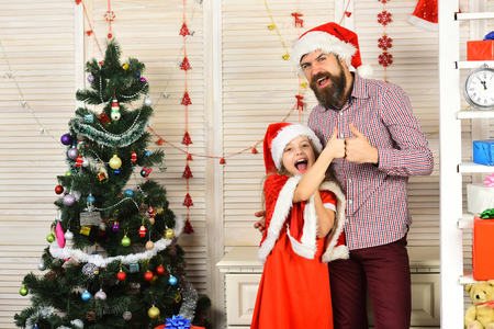 Christmas happy child and father with present box. Winter holiday and boxing day. New year small girl, man with gift. Xmas party celebration, fathers day. Santa kid, bearded man at Christmas tree.