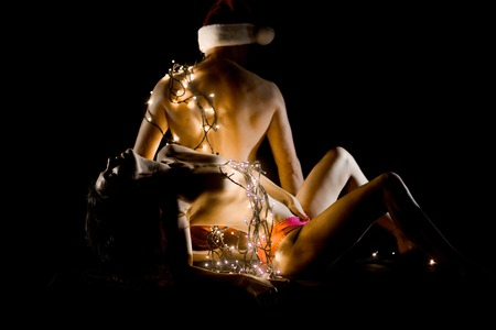 New year boyfriend and girlfriend isolated on black. Relations of couple in illuminated garland. Christmas couple in love of sexy man and woman. Love and sex games. Santa man and girl with naked body.