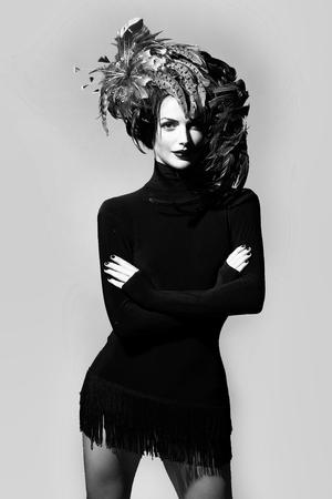 ハロウィーンやカーニバルの休日の衣装と灰色の背景に黒いドレスとして美しい羽の帽子茶色の色できれいな顔に赤い唇を持つ若いセクシーな女性 写真素材