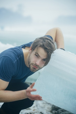 Cold weather and ice age. Winter holiday and activity. Power and strength of man with frozen hummock. Cracked ice at Hercules guy in Christmas. Man hold big ice block. Stock Photo