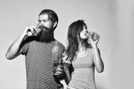 Attractive couple of beautiful long-haired girl and handsome bearded man drink water from bottles and glass on grey wall Stock Photo
