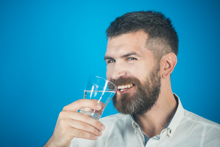 happy hipster drink clean healthy water, refreshing. Health and dieting. Life source and healthcare. Hangover and thirst. Man with long beard hold water glass on blue background, copy space Imagens - 91614922