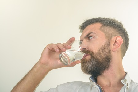 Hipster drink clean healthy water, refreshing. Man with long beard hold water glass isolated on white background. Life source and healthcare. Hangover and thirst. Health and dieting.