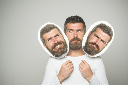 Hipster with sad face hold portrait nameplate. Guy or bearded man on grey background. Man with long beard and mustache. Barber fashion and beauty. Feeling and emotions. Banco de Imagens