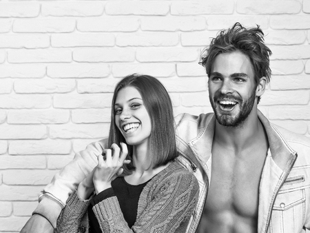 Happy young couple of handsome man or muscular macho in unzipped jacket with pretty cute girl or beautiful woman in knitted coat laugh on white brick background Stock Photo