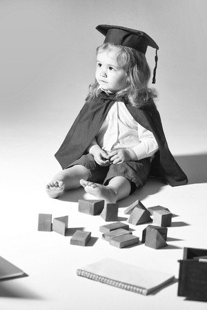 Small boy child with long blond hair in blue shirt black graduation gown and cap playing with wooden blocks and diaries isolated on white background