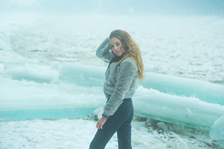 Winter holiday and vacation. Cracked ice background and woman in Christmas. girl with frozen hummock. Cold weather and ice age. woman with pretty face at ice block.