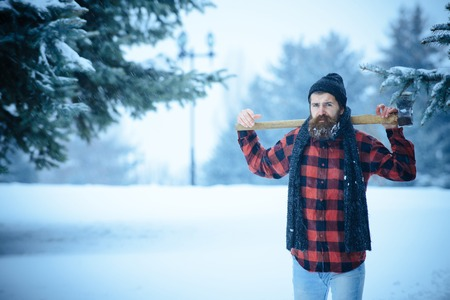 Winter holiday and celebration. New year man in snowy cold forest. Wanderlust, hiking and travel. Man with beard in winter forest with snow hold axe. Christmas hipster lumberjack with ax in wood..