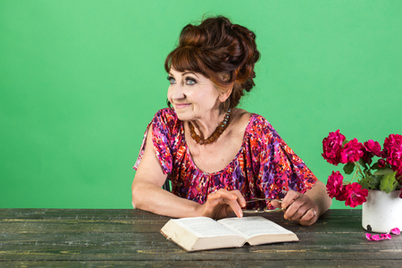 old lady or grandmother. Old woman reading book with glasses at flowers. Writer and poet, granny read fairytale. Pension and retirement, old age. Teacher or professor, education, teachers day.