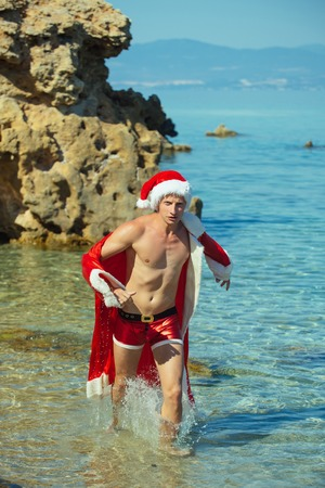 Santa claus muscular guy in red Christmas costume. Winter holiday vacation. New year man swim at beach. Xmas party celebration. Christmas happy man in water. Stock Photo