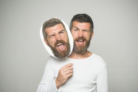 灰色の背景に紙のネームプレートを持つウインク顔に長いあごひげを持つ男