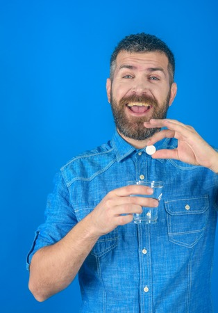 Man with beard hold water glass on blue background, headache. painkiller drug and antidepressant. Treatment, hypnotic tablet. Health and medicine, flu and cold. happy hipster drink pill with water.