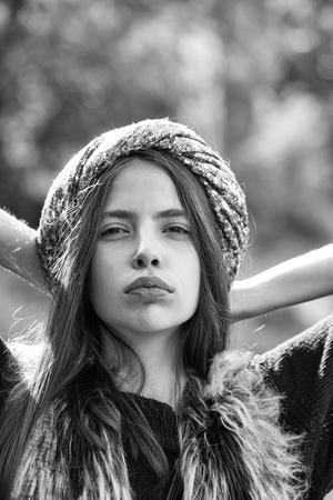 modieuze jonge sexy vrouw of meisje met mooi gezicht en lang brunette haar in grijze pailletten hoed of tulband en bont vest buiten op een onscherpe achtergrond
