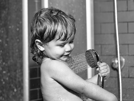 Cute happy smiling funny undressed boy child with blonde curly wet hair taking shower in bath with water indoor, horizontal picture Standard-Bild