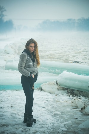 Winter holiday and vacation. girl with frozen hummock. Cold weather and ice age. Cracked ice background and woman in Christmas. woman with cute face at ice block. Stock Photo