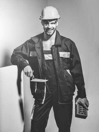 Happy man smiling handsome builder construction mason worker bricklayer in orange hard hat and boilersuit keeps brick and trowel on grey background Reklamní fotografie