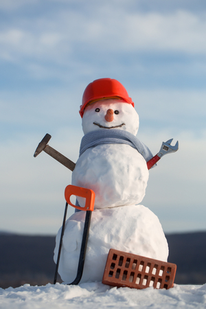 Christmas or xmas decoration. Snowman builder in winter in helmet. New year snowman from snow with saw and brick. Happy holiday and celebration. Building and repair work.