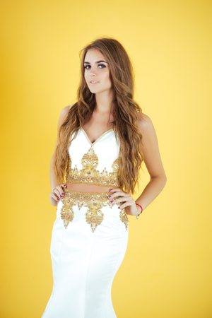 Girl with long brunette hair. Model with stylish makeup on yellow background. Holiday celebration concept. Fashion and beauty salon. Woman posing in evening dress.