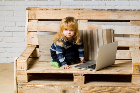Small boy blogging on bench, online buy. School and communication. Kid at computer with cell phone, sms and 4G. Social network and new technology. child with laptop and mobile phone, education.