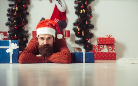 Santa claus man with gift pack. New year guy at Christmas decoration fireplace. Boxing day and party celebration. Christmas man with beard on sad face at present box. Winter holiday and xmas.