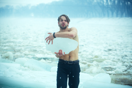 Man with bare muscular chest hold big ice block. Power and strength of man with frozen hummock. Cold weather and ice age. Cracked ice at Hercules guy in Christmas. Winter holiday and activity. Stock Photo
