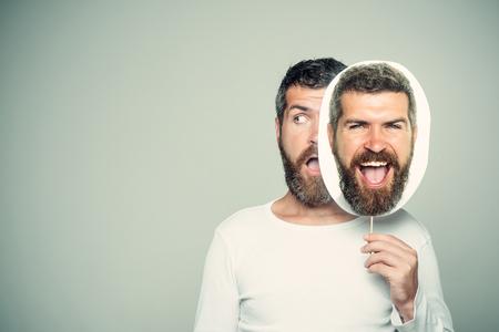 驚きと幸せな顔を持つヒップスターは、肖像画のネームプレートを保持します。長いあごひげと口ひげを持つ男。床屋のファッションと美しさ。感