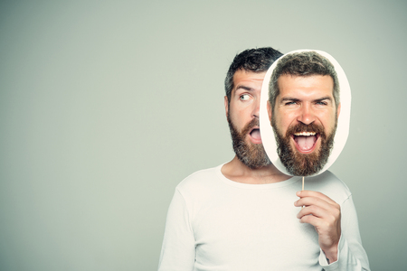 Hipster with surprised and happy face hold portrait nameplate. Man with long beard and mustache. Barber fashion and beauty. Feeling and emotions. Guy or bearded man on grey background., copy space Imagens