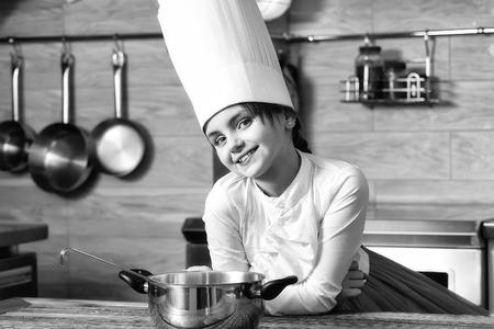 요리사 모자에 냄비와 작은 소녀. 요리, 음식, 공부
