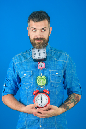 Time and perfect morning. Man with beard hold alarm clock. Overtime and urgency. Time management and countdown. Lifetime, business and deadline. Stock Photo