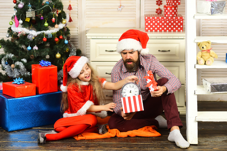 Happy family celebrate new year and Christmas. Father and child with present box. Winter holiday and New year. Father and daughter in santa hat at Christmas tree. Xmas party celebration. Stock Photo
