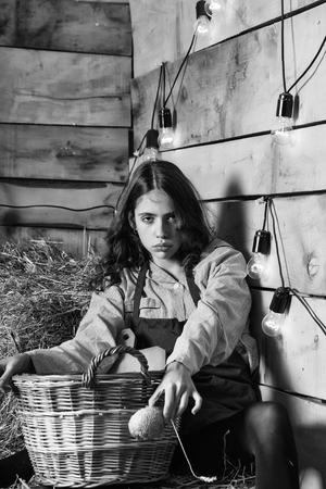Pretty girl teenager young woman cookee helper in apron sits on straw bales with wicker basket and bun bread on rustic background Reklamní fotografie