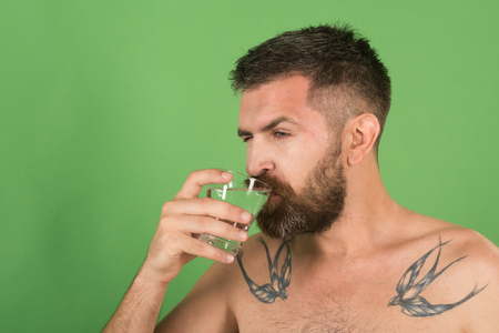 Life source and healthcare. Hangover and thirst. Hipster drink clean healthy water, refreshing. Health and dieting. Man with long beard hold water glass on green background. Imagens