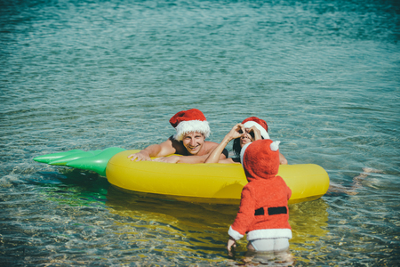 christmas happy family and child in red santa claus hat at sea or ocean water beach with pineapple mattress, summer and winter vacation, new year holiday and party celebration, love and childhood Stock Photo