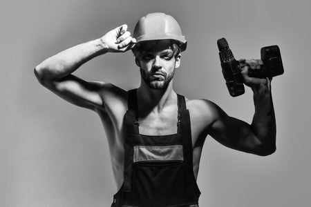 Handsome man builder repairman craftsman foreman or construction worker in orange hard hat and overall with drill on grey background