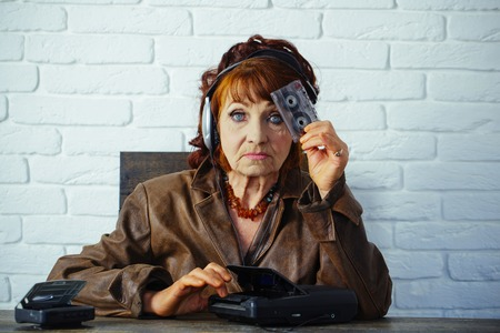 Audio book and new technology, education. Old woman with cassette recorder listen music in headphones. Spy and operator. Old school music player, radio. Granny dj in headset with cassette player.