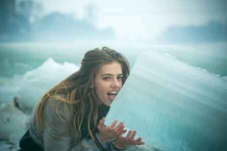 Winter holiday and vacation. woman with happy face lick ice block. Cracked ice background and woman in Christmas. girl with frozen hummock. Cold weather and ice age.