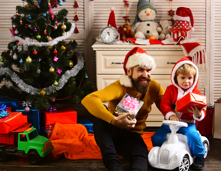 Happy family celebrate new year and Christmas. Father and child on car with new year present box. Father and son in santa hat at Christmas tree. Winter holiday and boxing day. Xmas party celebration.
