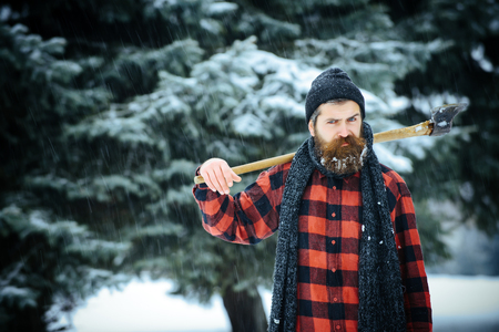 Winter holiday and celebration. New year man in snowy cold forest. Man with beard in winter forest with snow hold axe. Christmas hipster lumberjack with ax in wood.. Wanderlust, hiking and travel. Banco de Imagens