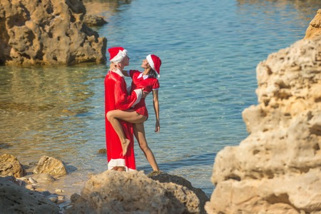 Winter holiday and vacation. Xmas party celebration and activity. New year girl and guy as santa. Christmas couple in red at beach. Couple in love of happy man and woman in water.