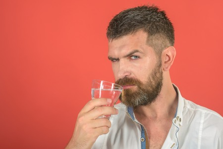 Man with long beard hold water glass on red background. Hipster drink clean healthy water, refreshing. Health and dieting. Hangover and thirst. Life source and healthcare, copy space
