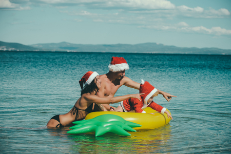 Santa child, parents at Christmas. Xmas party celebration, fathers and mothers day. Winter holiday vacation. New year man, girl with small boy. Christmas happy family on pineapple mattress in water.