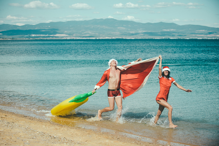 New year girl and guy as santa. Xmas party celebration and activity. Winter holiday and vacation. Christmas couple with pineapple inflatable mattress. Couple in love of happy man and woman in water.