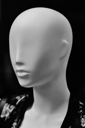 Fashion female mannequin bald in leisure wear clothes in shop on dark background