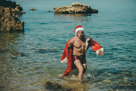 Santa claus muscular guy in red Christmas costume. Xmas party celebration. Winter holiday vacation. New year man swim at beach. Christmas happy man in water.