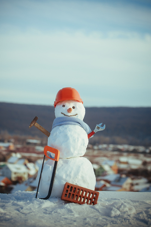 Building and repair work. New year snowman from snow with saw and brick. Christmas or xmas decoration. Happy holiday and celebration. Snowman builder in winter in helmet.