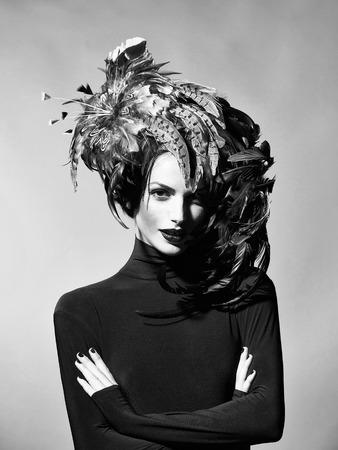 jonge sexy vrouw of meisje met rode lippen op mooi gezicht in mooie veer hoed bruine kleur als Halloween of carnaval vakantie kostuum op een grijze achtergrond